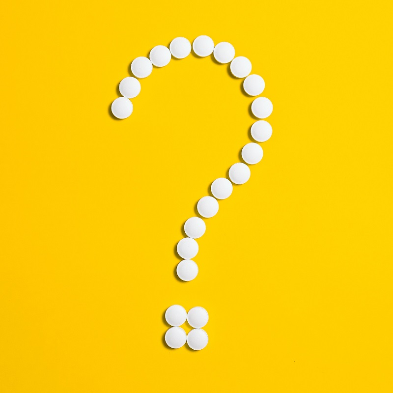 image of question mark with white pills yellow background